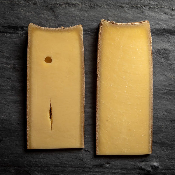 saxelby cheesemongers connoisseur's club fall selection - two different wedges of the same cheese on a cheese board at different ages