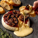 Baked Brie set - a gooey cheese toasted with nuts and strawberry jam with sliced baguettes