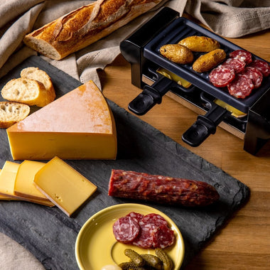 Raclette party set - raclette cheese, raclette machine with potatoes and salami, bread, and cornichons