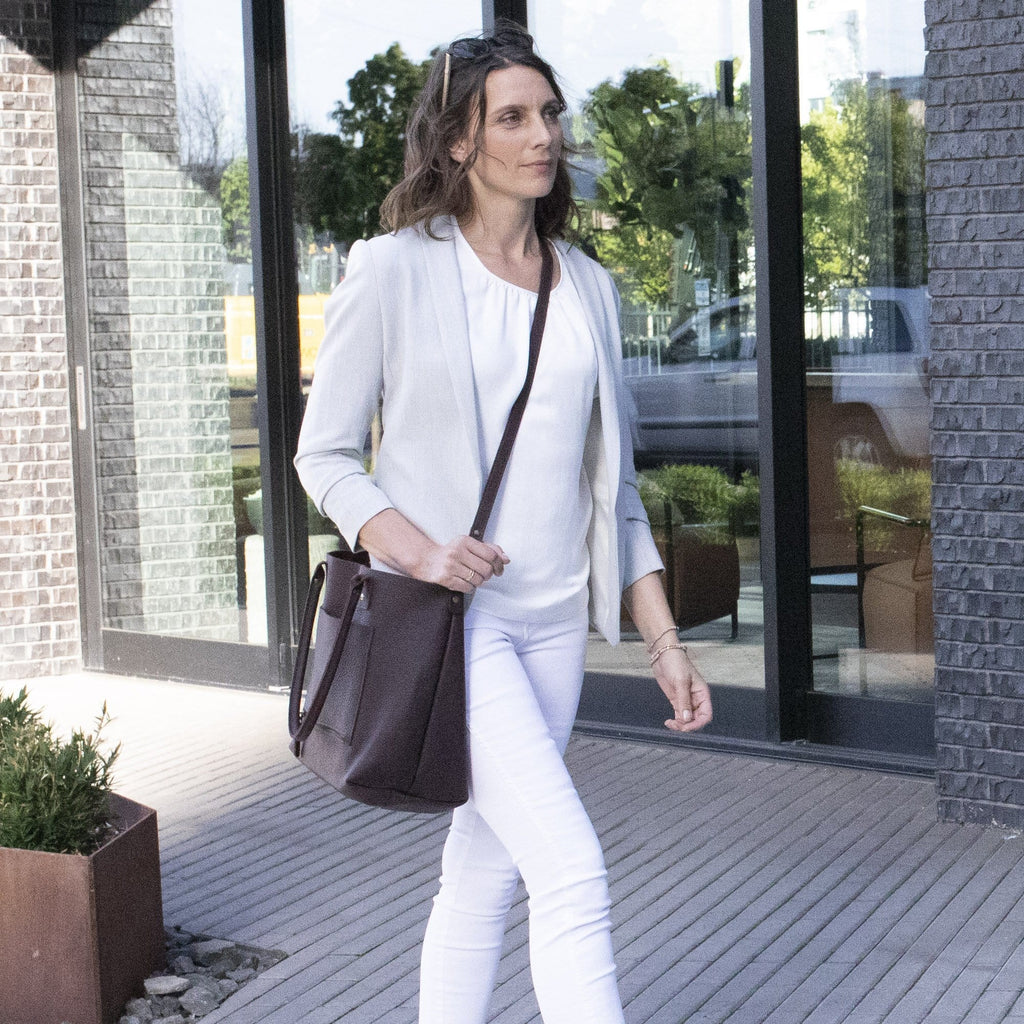 A woman walking with The SUMNER™ Crossbody Tote - Pebbled Black