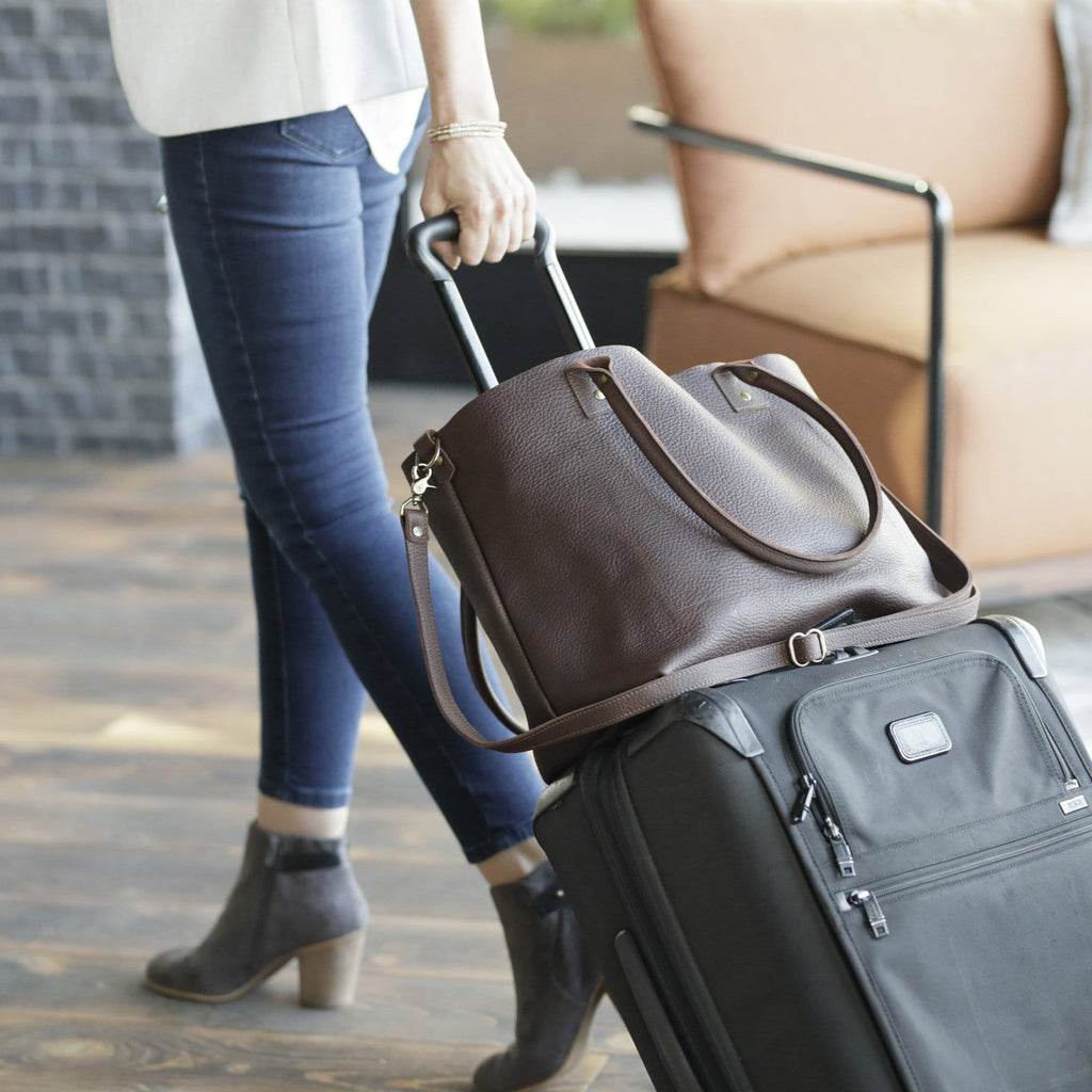 a woman walking with The SUMNER™ Crossbody Tote - Pebbled Black attached to luggage
