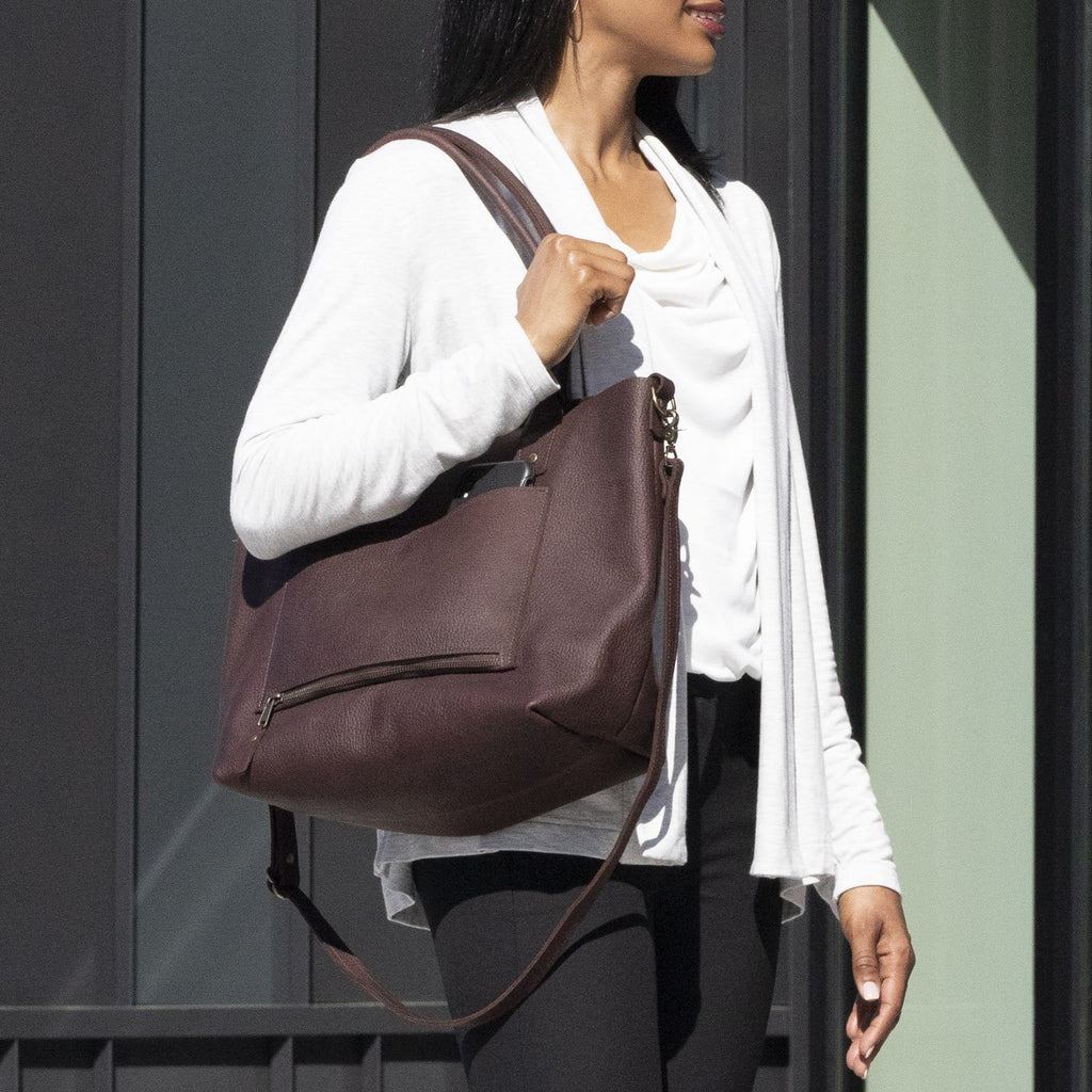 a woman outside holding the The SUMNER™ Crossbody Tote - Pebbled Black