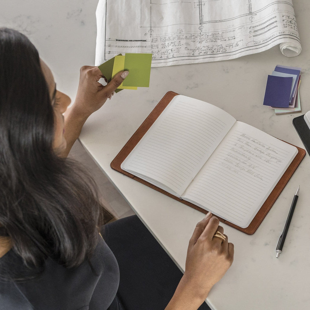 top view of a woman taking notes in The MERCER™ Refillable Journal - Small - Tan