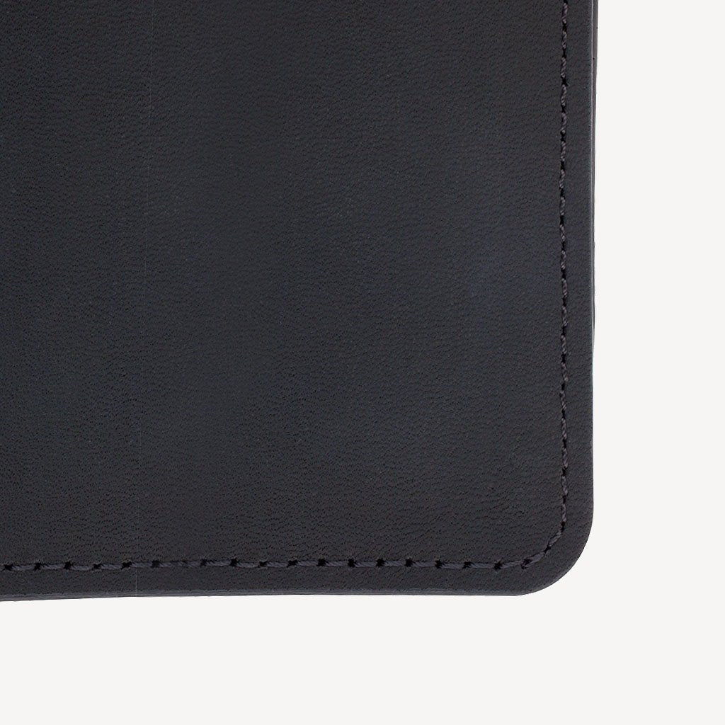 a closeup on The SAND POINT™ Passport Holder - Black showing the quality leather