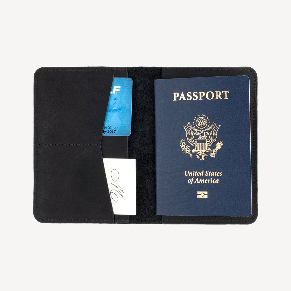 The SAND POINT™ Passport Holder - Black - Open with a passport and particulars inside