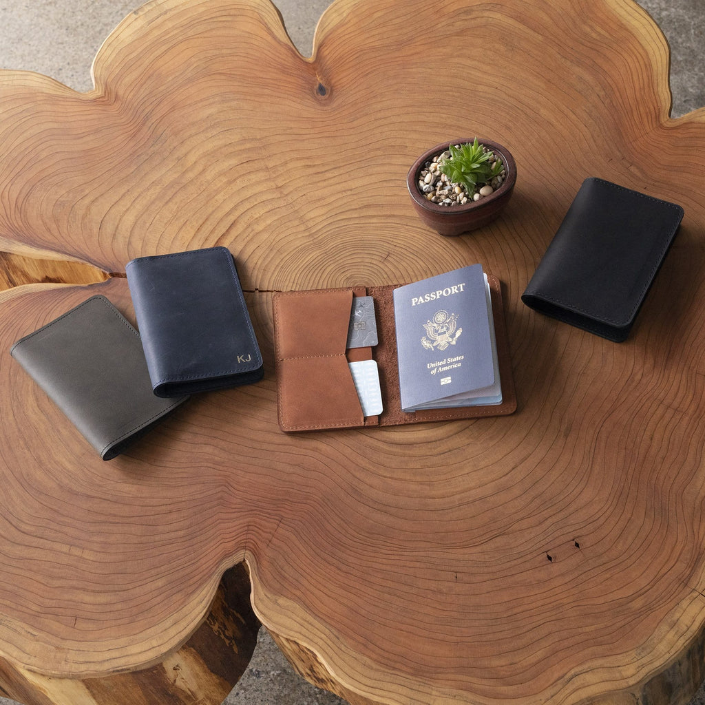 The SAND POINT™ Passport Holder - Black on a brown wooden table