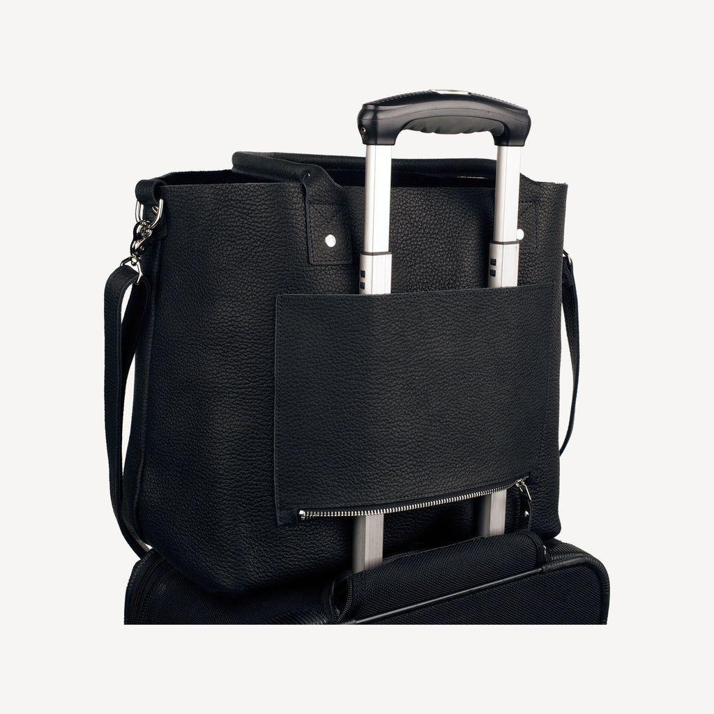 The SUMNER™ Crossbody Tote - Pebbled Black showing the luggage attachment feature