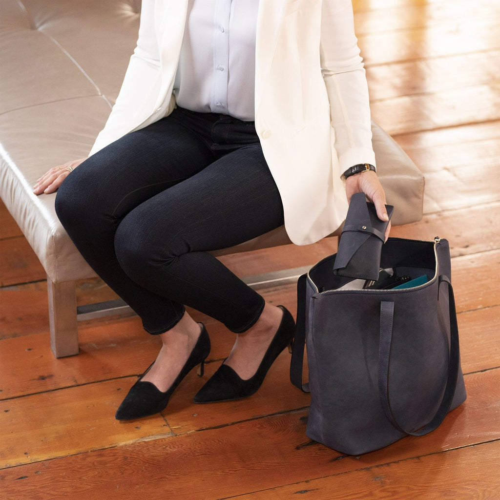 A lady sitting on a bench holding The BALLARD TOTE™ - Tan