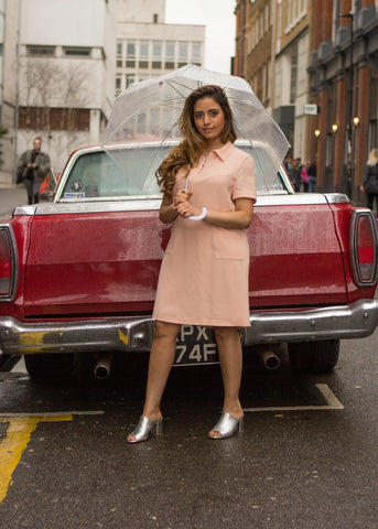 Woman dressed in a petite blush polo dress standing by vintage car