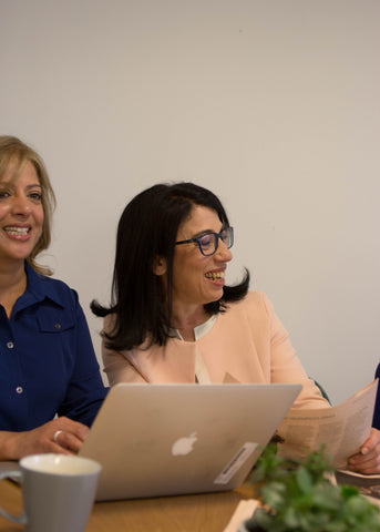 Two women laughing in a meeting
