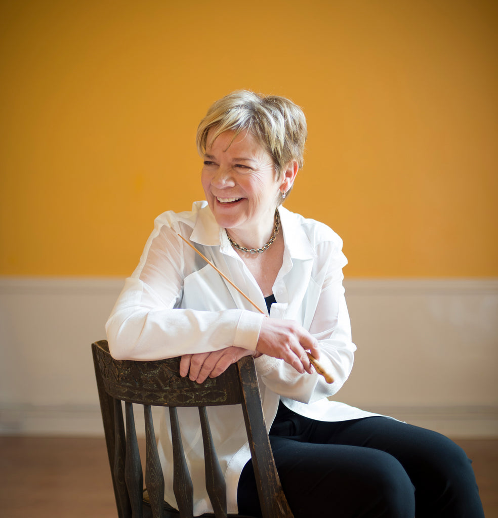 Marian Alsop conductor sitting in chair with baton