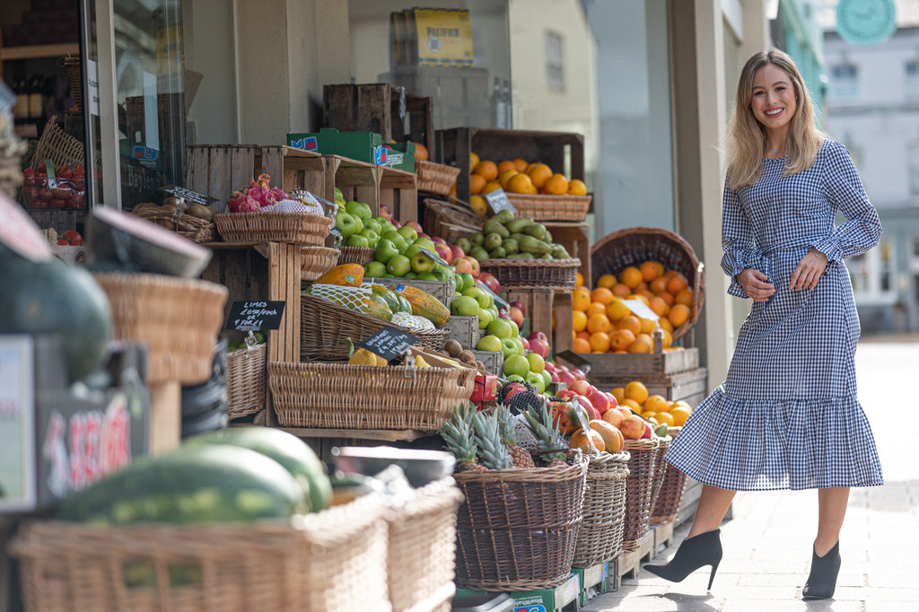 Petite model in gingham dress in front of fruit stall
