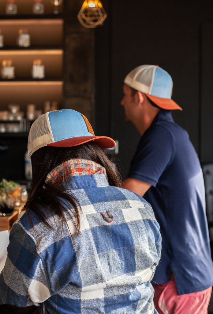 Couple at a bar with Maroon Bell apparel flannel and trucker hats