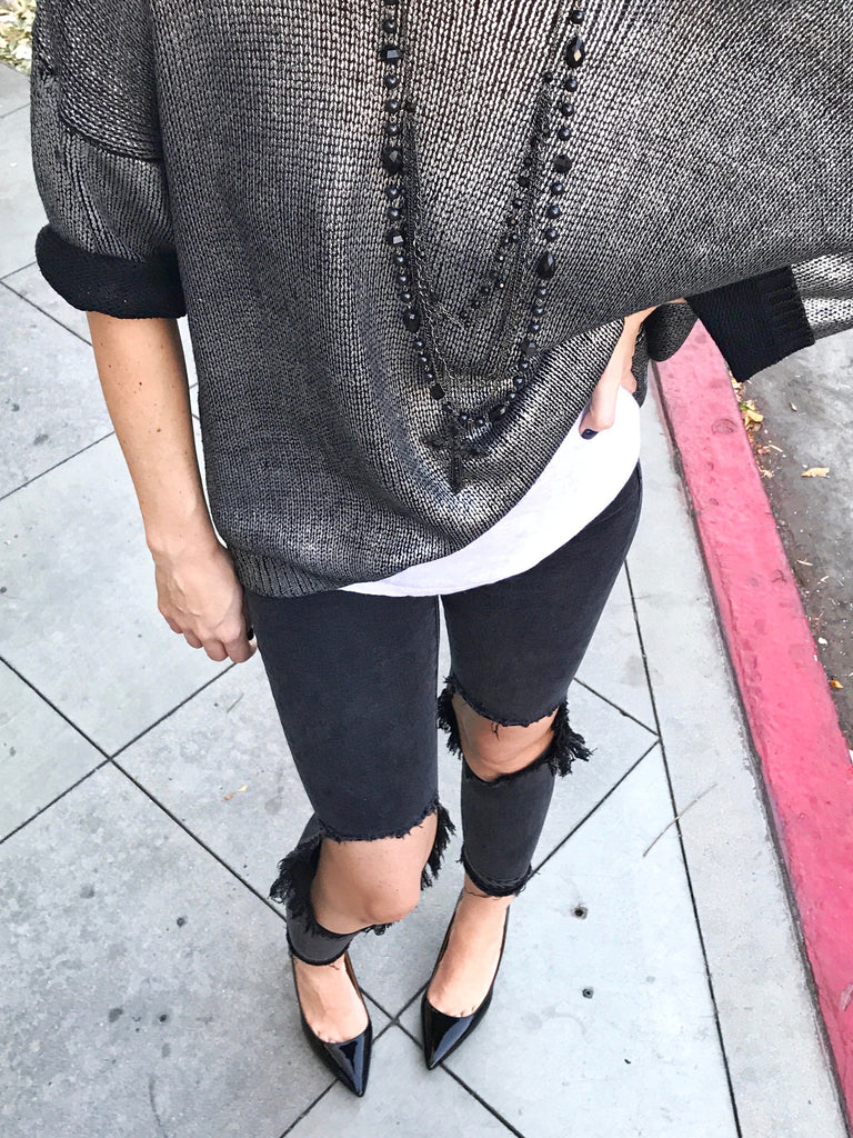 closeup of sweater and black skinny jeans