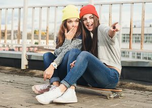 Two girls sitting on a long board and wearing beanies