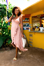 Model walking by coffee bar in Hawaii wearing polka dot high-low wrap dress with ruffles.