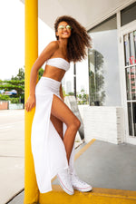 Beautiful black model wearing sheer maxi skirt in white colour. High waisted skirt with high slit.