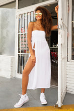 Beautiful black model wearing sheer white maxi dress. Dress has bandeau neckline and high slit.