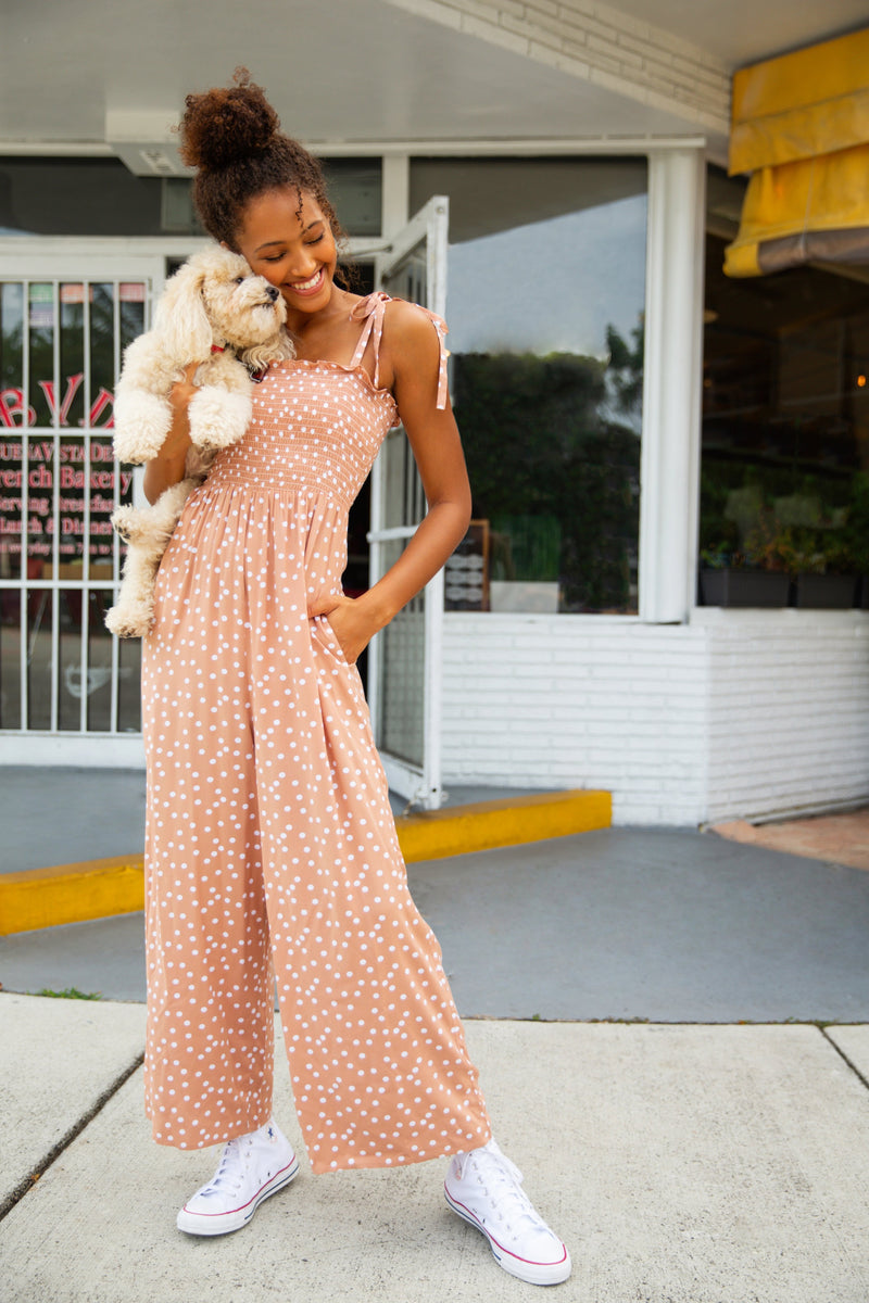 Model outside of cafe in Miami Florida. Model holding a small puppy. Model wearing a honey bronze coloured jumpsuit with tie straps, a bandeau ruched chest area and polka dots on fabric. Jumpsuit has pockets.