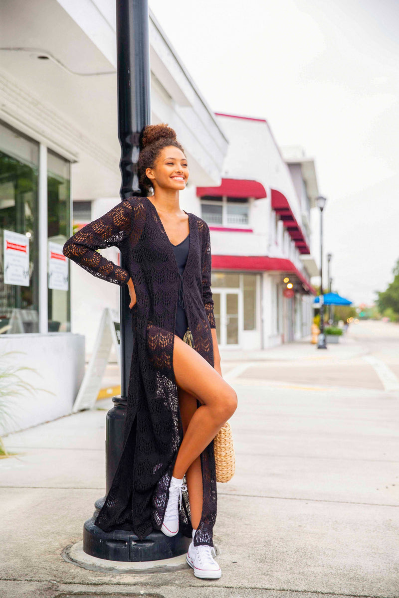 Model smiling wearing a long floor length black lace cardigan. Model posed leaning on a street lamp in Miami Florida.