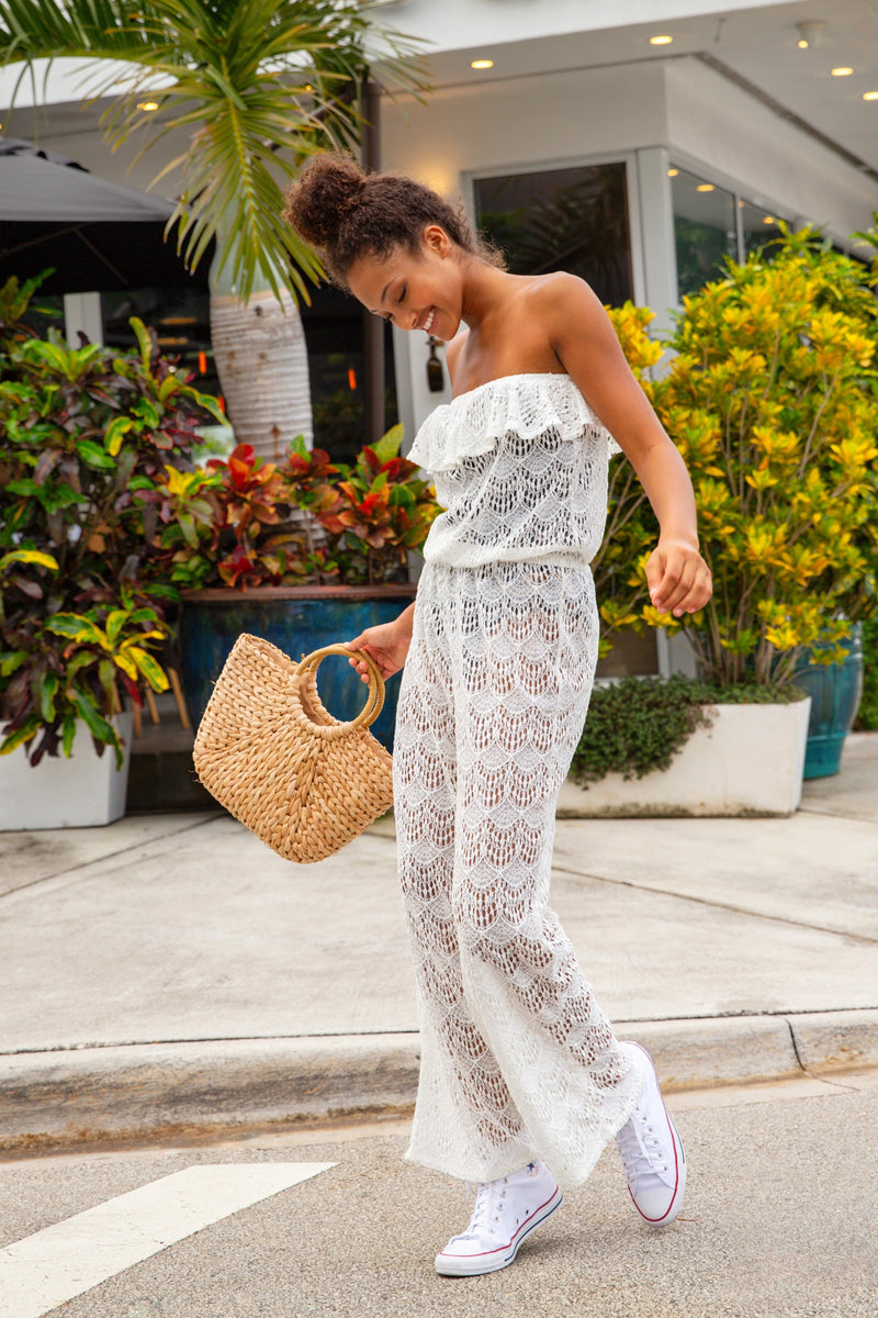 Model dancing in street in Miami Florida. Model wearing white lace bandeau ruffle jumpsuit and converse shoes.