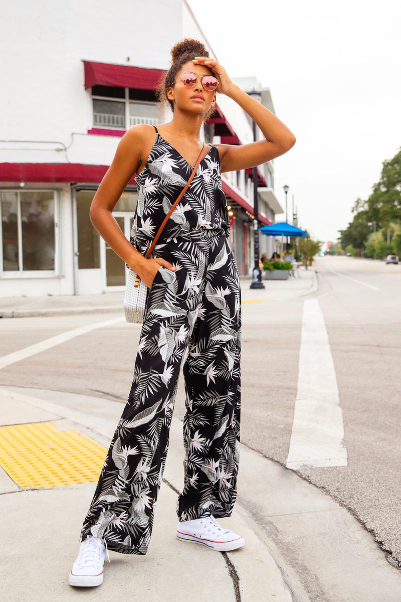 MODEL IN MIAMI POSING ON STREET WEARING FLORAL PALM PRINT CAMISOLE TOP AND MATCHING STARIGHT LEG PANTS. SHOES ARE WHITE CONVERSE, SUNGLASSES AND CROSS BODY BAG USED FOR ACCESSORIES.