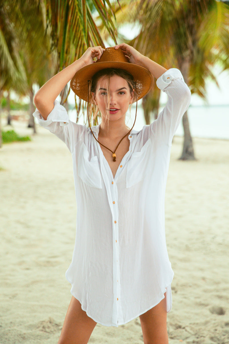 Blonde model on beach in Miami Florida. Model wearing sheer button up bikini coverup. Model wearing straw hat.
