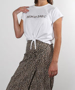Matching leopard print set. T-Shirt crop top with beach babe writing on front flowy pants with elastic waistband in leopard print pattern. Made in collaboration with vancouver and women-owned business brunette the label. Made for boss babes to wear as dinner outfit inspiration, an outfit for the beach, an outfit for vacation, or when at a resort exploring local attractions.