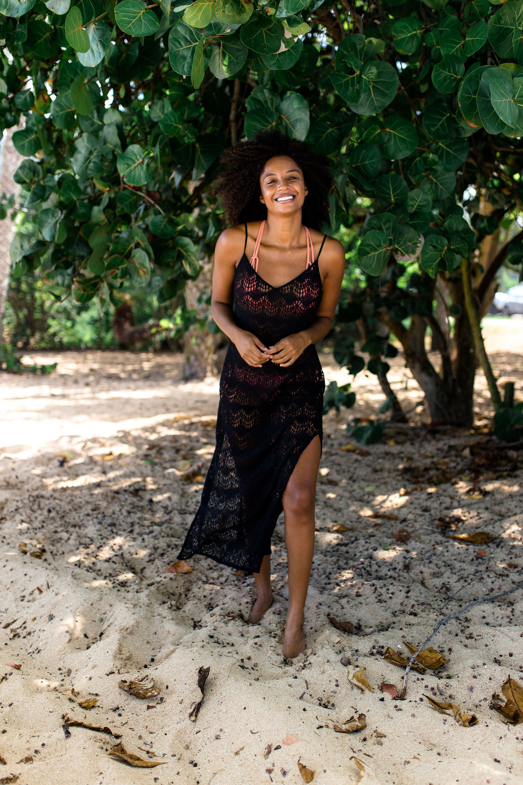 Model smiling on a beach in Hawaii. Model wearing black full lace maxi slip dress with a slit on left leg.