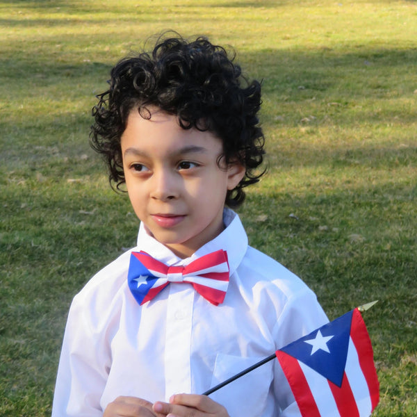 Boy holding flag wearing Puerto Rico flag bow tie