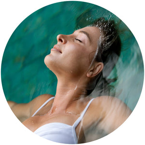 Woman relaxed deeply floating in water, guided by intuition, symbolising the deep peace and inner healing Whole Brain Technology Music can bring to listeners
