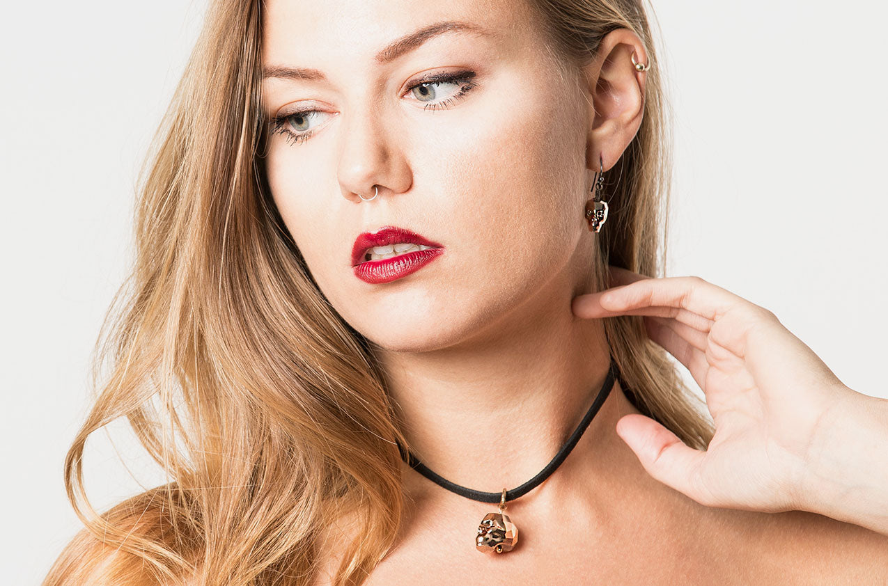 Blonde model wearing Lovely Bones Swarovski Skull earrings Rose Gold with black sterling silver earwires