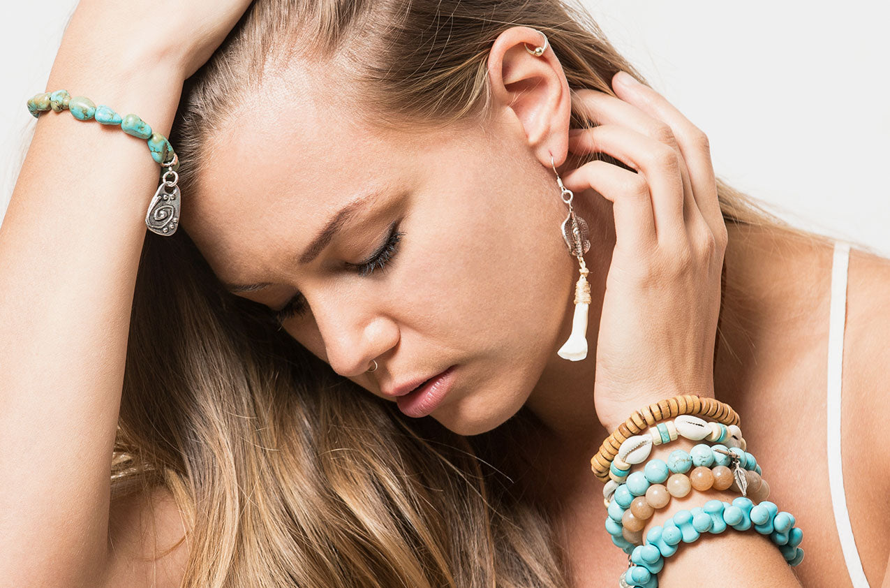 Blonde model wearing Metal & Bone. Tribal drop earrings