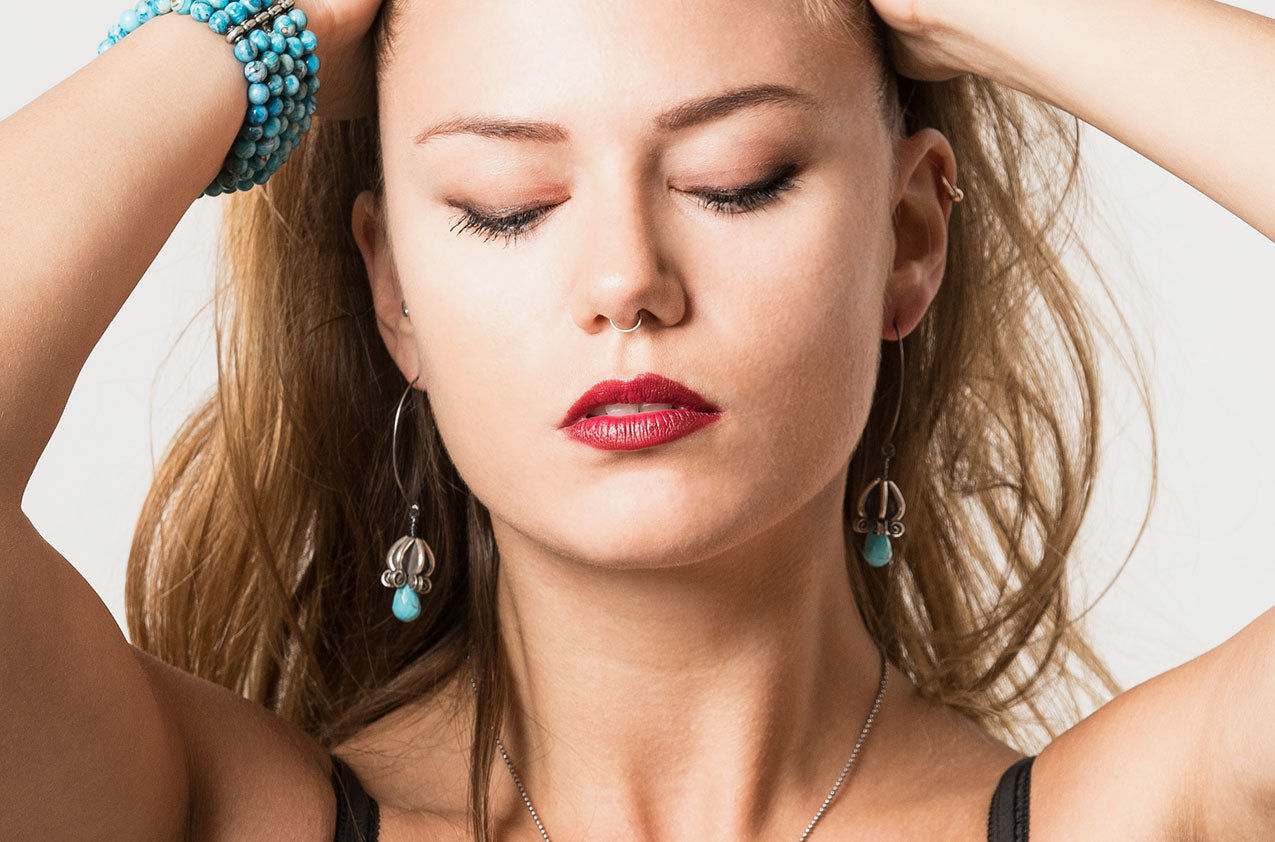 Blonde Model wearing Silver & Stone. Artisan turquoise earrings