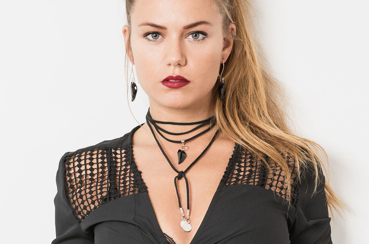 Blonde model wearing Wolf's Tooth. Swarovski drop Jet earrings