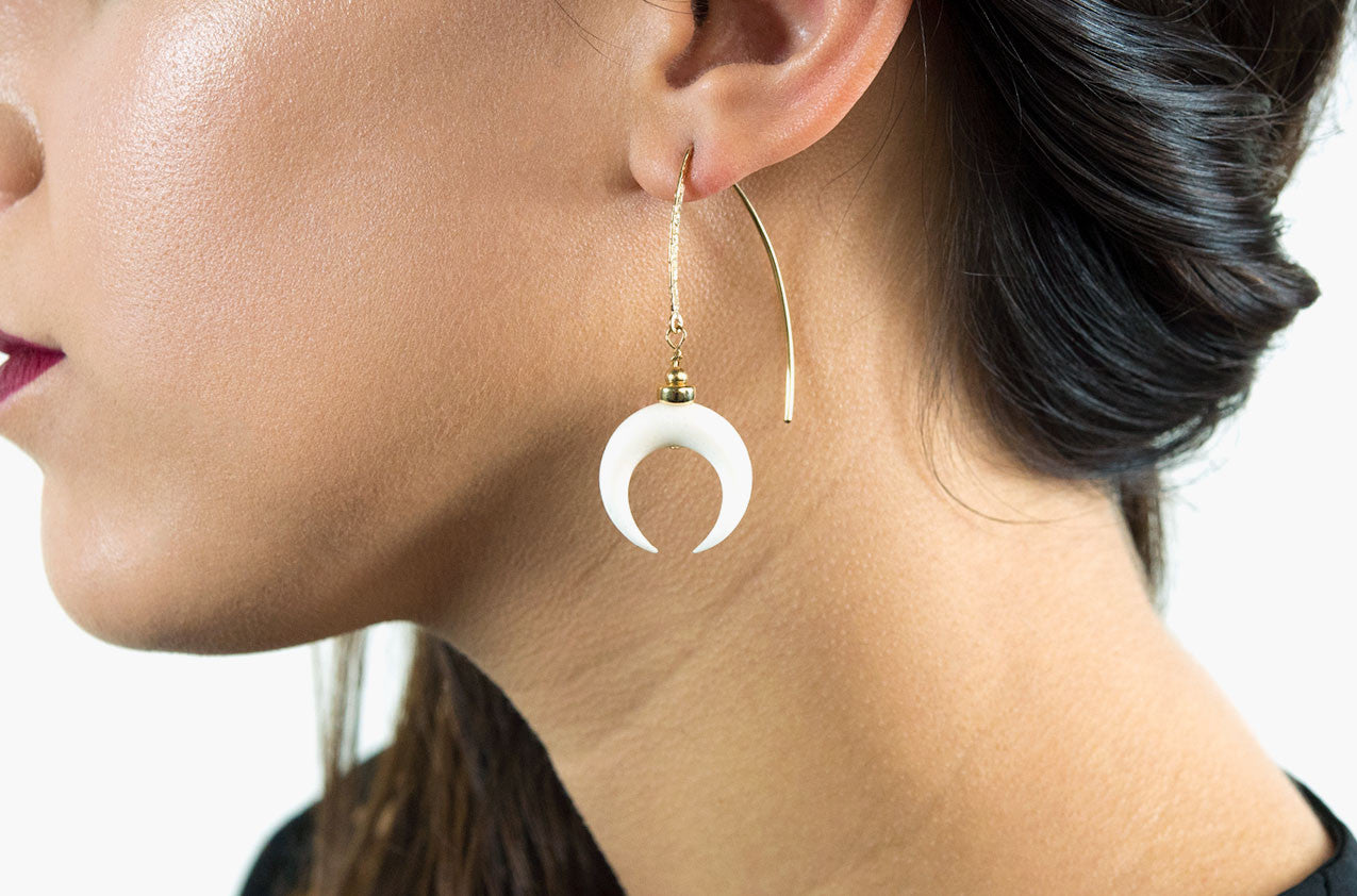 Model wearing Little Big Horn. Crescent medium drop earrrings Ivory with 14kt gold hammered earwires