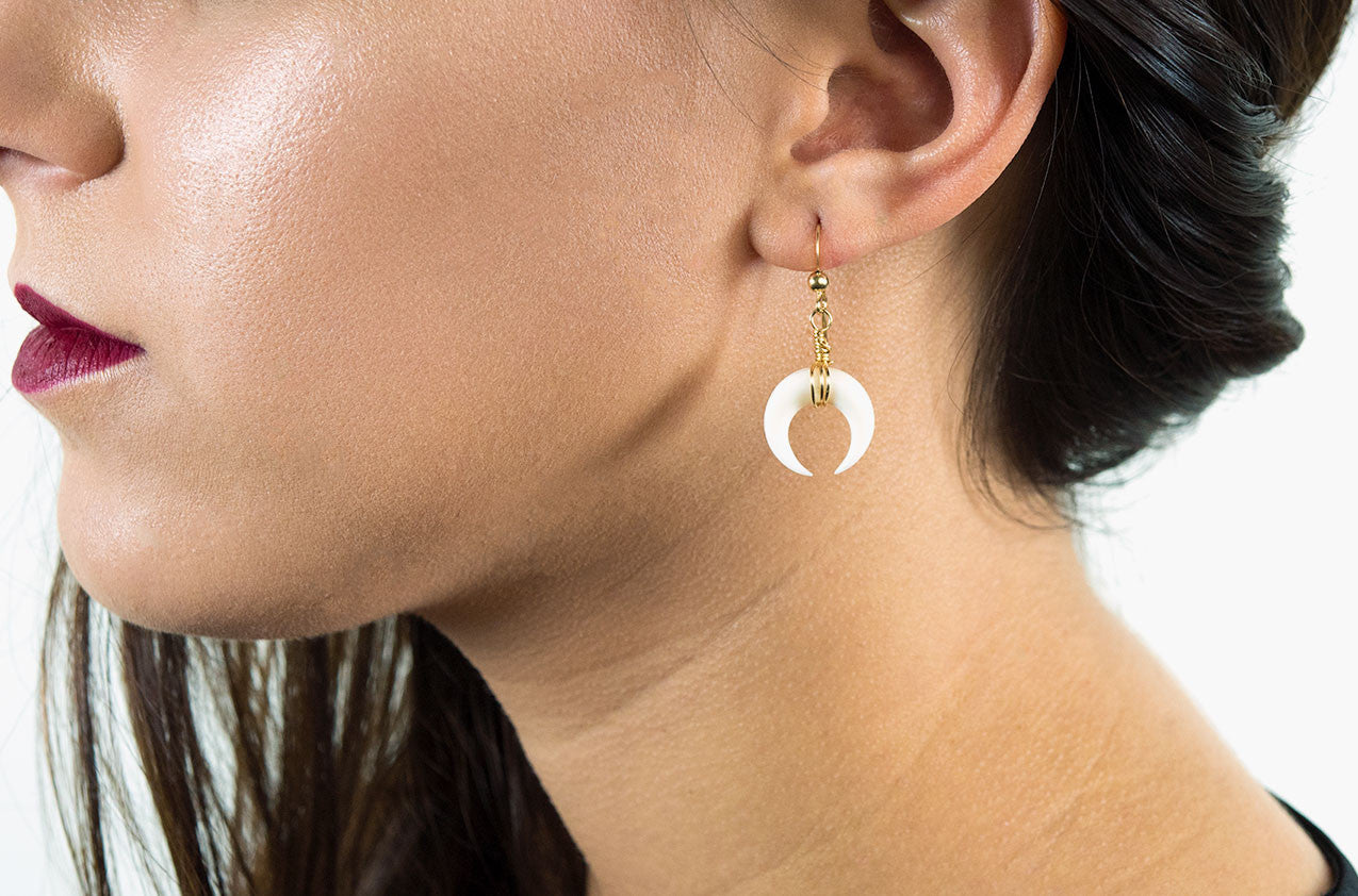 Model wearing Little Big Horn. Crescent mini wire-wrap earrings Ivory with 14kt gold-filled earwires