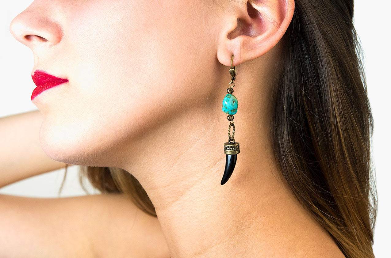 Model wearing Metal & Stone. Brass and turquoise earrings