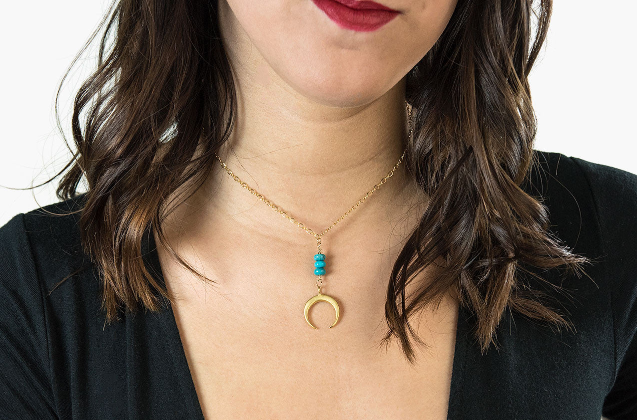 Model wearing Metal & Stone. Turquoise and precious metal crescent gold