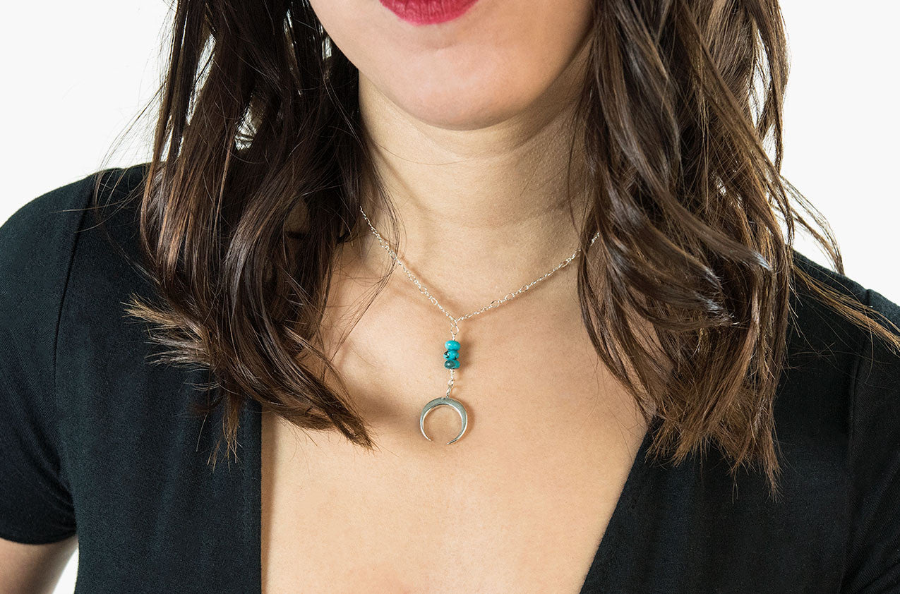 Model wearing Metal & Stone. Turquoise and precious metal crescent silver