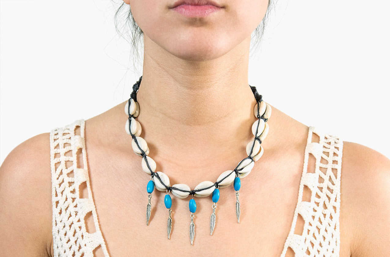 Model wearing Shell, turquoise and arrow charm necklace