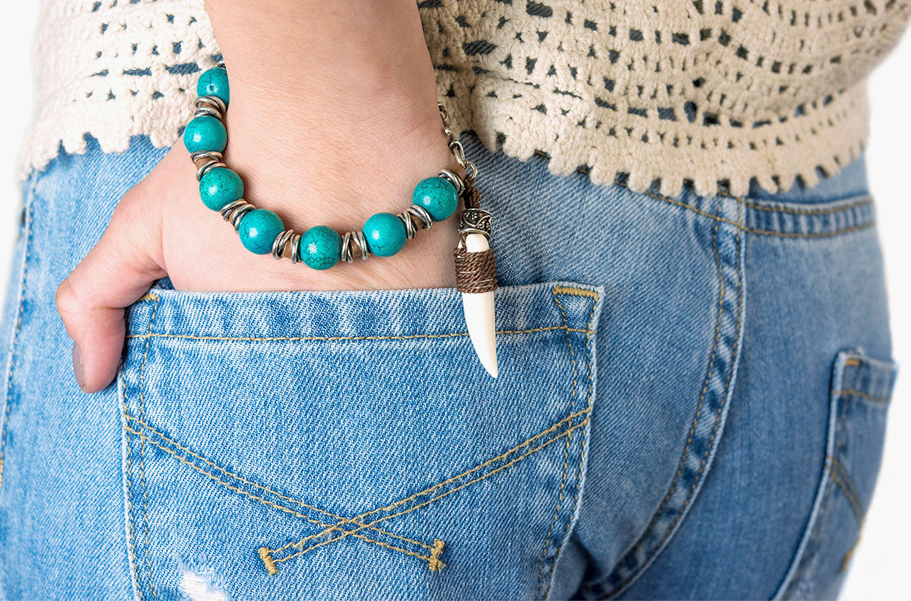 Model wearing Stone & Bone. Turquoise and tooth bracelet