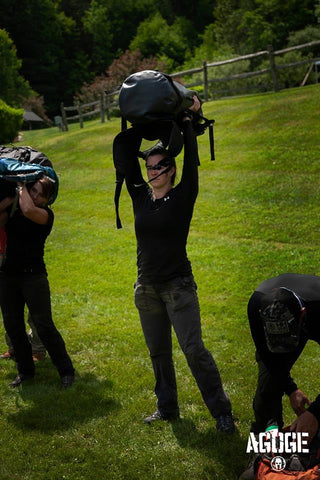 Rachel Lotz carries lifts her Rockagator AGOGE pack over her head in an endurance challenge