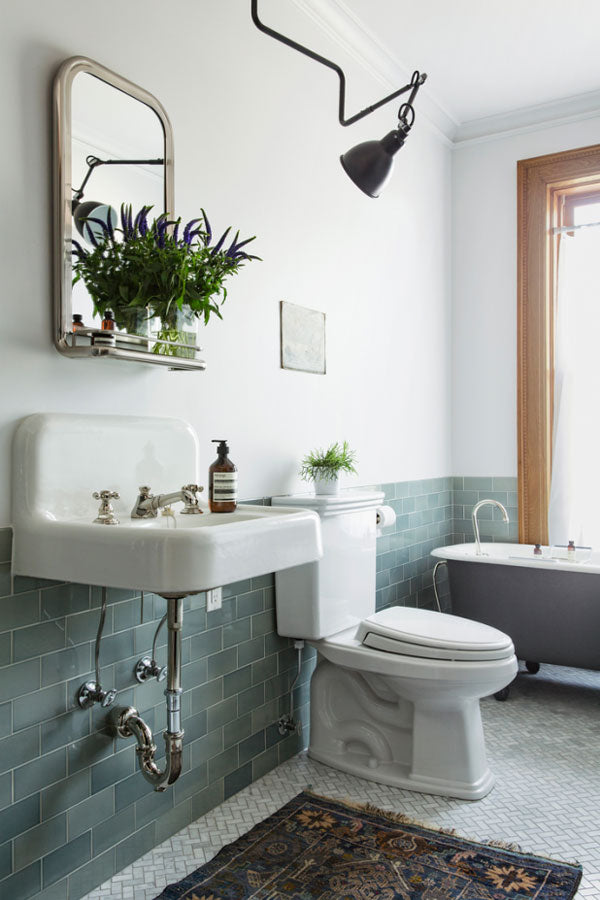 Bathroom with teal blue subway tiles, old style sink, warm wood and an antique rug