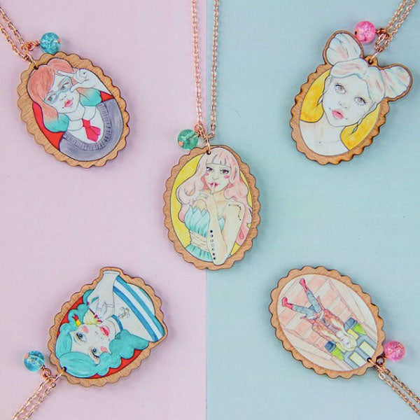 All five of my wood and rose gold illustrated necklaces on Instagram