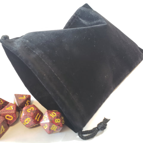 Large black dice bag with dice rolling out on a white background.