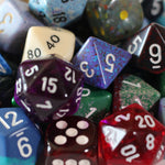 assortment of multi-sided dice of varying color and design