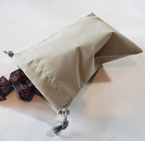 small gray dice bag with dice spilling out.  On a white background