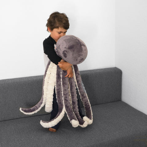 Little kid holding a giant octopus plush toy