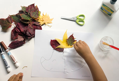 Picture of a kid hand gluing leaves to a hedgehog